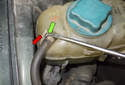 Working at the top of the coolant expansion tank, using a flathead screwdriver, release the hose retaining clip (green arrow) by prying it up.