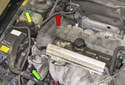 The power steering reservoir is mounted on the right side of the engine compartment, on the strut tower (yellow arrow).