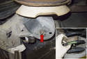 Working below the trailing arm, remove the 15mm spring retainer nut (red arrow).
