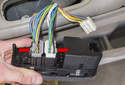 Then disconnect the power window switch electrical connectors by pressing the release tabs (red arrows) and pulling them straight out.