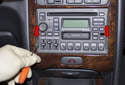Use a small flathead screwdriver or plastic lever and press the radio pulls in (red arrows).