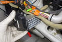 Push the wiring harnesses in front of the blower motor resistor up and hold them out of the way.