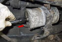 Once the fuel filter is installed into the clamp, press the fuel lines onto the fuel filter (red arrow) until they stop.