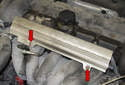 Remove the two 10mm fuel rail fasteners (red arrows).