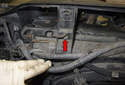 Working at the left side of the radiator, remove the 8mm fan shroud fastener (red arrow).
