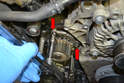 Slip the timing belt off the coolant pump and remove the three 10mm bolts (red arrows, two shown).