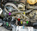 With everything removed you can now have access to all the components on the front of the motor: the cam sprocket (purple arrow), belt tensioner (red arrow), rollers (yellow arrows), crankshaft sprocket (blue arrow) and the coolant pump (green arrow).