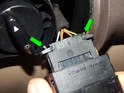 Press the tabs on the rear of the electrical connector (green arrows) and pull the connector off.