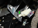 Unscrew the brake light switch from the mounting plate (green arrow).