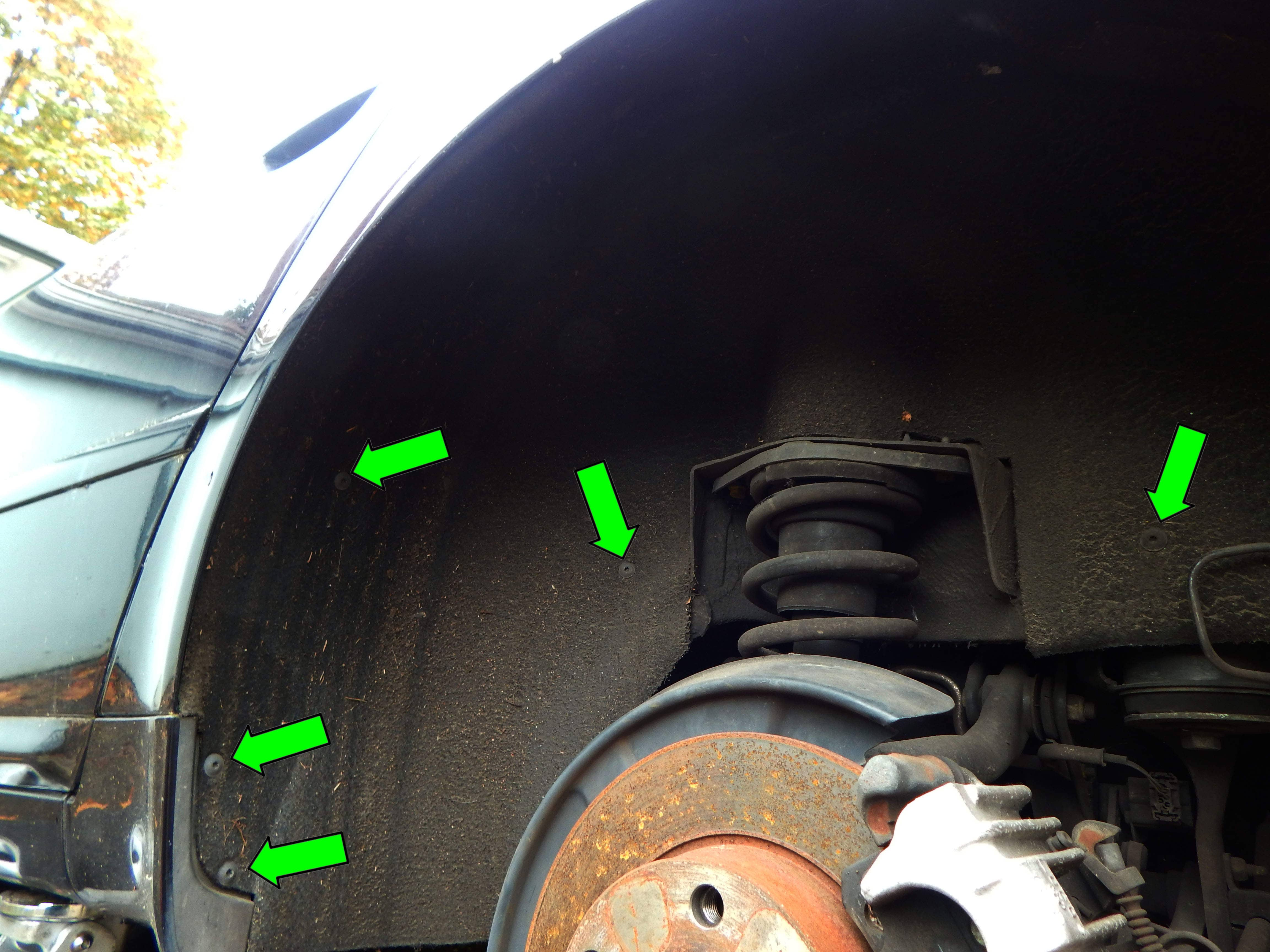 Begin by removing the T25 Torx screws (green arrows) around the front and center of the wheel liner as shown here.