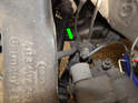 Once the brake pad wear indicator is disconnected, pull the ABS sensor wiring harness out of the metal locating tab (green arrow).