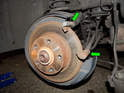 Removing the disc requires removing the caliper mounting frame (green arrows) from the rear of the wheel hub.