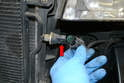 Disconnect the sensor from the left side of the condenser by releasing the tab and pulling it straight off (red arrow).