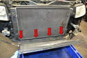 Remove the four T20 Torx screws holding the lower air trim piece on the bottom of the radiator (red arrows).