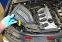 On the upper right side of the engine bay remove the two fasteners from the cross member (red arrows) and pull the intake air (yellow arrow) from the engine bay.