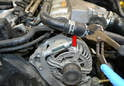 Use a set of pliers or Channel Locks and remove the clamp for the coolant hose above the alternator (red arrow).