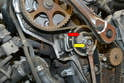 While holding the tensioner in place with an 8mm Allen (red arrow), use a 13mm socket or wrench and loosen the nut holding the tensioner in place (yellow arrow).