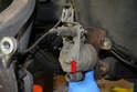 Use a 10mm wrench and remove the single bolt (red arrow) that holds the accessory bracket to the caliper.