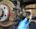 Pull the caliper (yellow arrow) off from its mount leaving the brake pads (red arrow).
