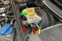 With the cover off you can see the reservoir and cap (green arrow) and where the master cylinder attaches to the brake lines ((red arrows).
