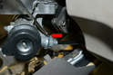 Use a small flathead screwdriver and gently lift retaining clip on the interlocking cable on the back of the ignition assembly (red arrow).