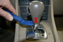 Use a trim removal tool and gently insert it between the leather base and chrome bezel on the shift knob.