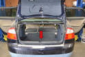 Begin by removing the trunk cover or carpet that covers the rear compartment (red arrow).