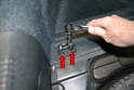Use a T30 Torx and remove the four screws holding the two tie down brackets in place (red arrows).