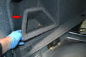 Remove the rear storage compartment on the left side by tilting it towards the center of the trunk and pulling up (red arrow).