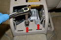 Use a 13mm socket and remove the two bolts on the rear of the console (red arrows).