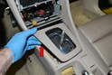 Open the ashtray and gently pry up and remove the trim piece around the shift mechanism (red arrow).