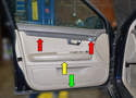 There are three areas on the door panel where you will need to remove Philips head screws: the first is under the trim piece (red arrows), the second is under the doors pulls in the arm rest (yellow arrow) and the third is the single screw on the bottom center of the panel (green arrow).
