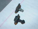 This photo compares the plastic and metal fasteners used to secure the undertray.