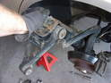 Tilt the strut assembly outward and use it to push the lower control arm down in order to let the top of the assembly clear the fender lip.