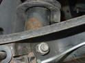 The lower shock bolt runs through the lower control arm.