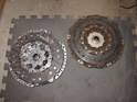 The new clutch disc and pressure plate are on the left, the old on the right.