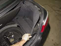 Replacing battery: Remove the battery trim panel cover from the trunk.