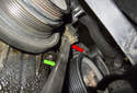 Accessory belt tensioner: Using a pry bar (green arrow), gently lever the tensioner (red arrow) away from the engine.