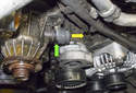 Working at the left side of the coolant pump, use a flathead screwdriver to lever out the coolant hose retaining clip (green arrow).