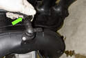 NG6 6-cylinder engines: Working at the rear bottom of the plenum on the intake manifold, squeeze the crankcase breather hose release collar and remove it from the intake manifold (green arrow).