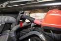 Unclip the battery cable from the strut tower brace by opening the mount (red arrow).