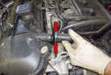 Working at the left front corner of the cylinder head cover, disconnect the crankcase vent hose by squeezing the release tabs (red arrows) and pulling the hose away from the cylinder head cover.