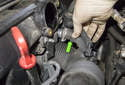 Then, pull the idle air control motor boot (green arrow) off the idle control motor.