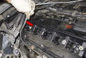 Continue to remove the oxygen sensor wiring harness from the valve cover by detaching it at the rear (red arrow).