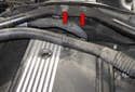 Working at the center of the wiper cowl above the valve cover, remove the two T45 Torx fasteners (red arrows).