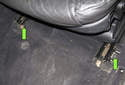 Front Seat: Then, remove the two T45 Torx mounting fasteners (green arrows) at the seat rails.