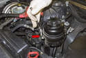 First, you will have to remove the power steering reservoir from its mounting bracket.