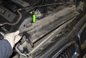 Lift the plastic cover up and off the radiator in the direction of the green arrow.