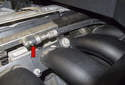Normally aspirated engine: Working at the center of the fuel rail, you will have to remove the fuel supply line (red arrow).