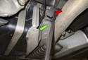 Working at the center muffler hanger, behind the fuel tank (green arrow), lever the rubber hanger off the support using a pry bar (red arrow).